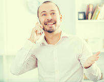 Positive young man calling by smartphone. Portrait of smiling young worker with his smartphone in office Royalty Free Stock Photo