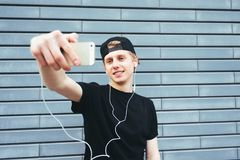 Positive young man in a cap and a black T-shirt makes selfie and listening to music on the background wall. Positive young man in a cap and a black T-shirt Stock Photography