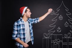 Positive young man decorating a Christmas tree. Stock Photos