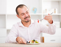 Positive young man eating greek salad Stock Image
