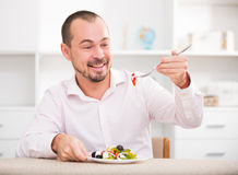 Positive young man eating greek salad royalty free stock image