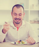 Positive young man eating greek salad Royalty Free Stock Photos