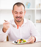 Positive young man eating greek salad Stock Photos