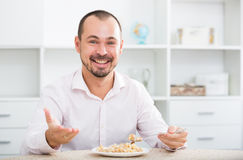 Positive young man eating porridge Stock Photos
