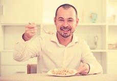 Positive young man eating porridge Stock Photos