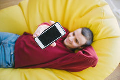 Positive young man hipster sends phone camera while sitting in a yellow chair bag. focus on the phone. Positive young man hipster sends phone camera while Royalty Free Stock Photography