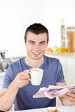 Positive young man holding a cup and a newspaper Stock Photo