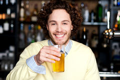 Positive young man holding a glass of beer Stock Image