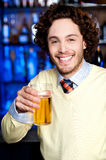 Positive young man holding a glass of beer Royalty Free Stock Image