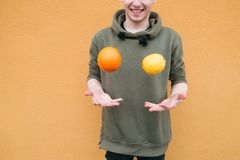 Positive young man juggles with lemon and orange on the background of an orange wall. Concept Fruit stock photography
