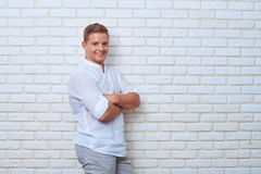Positive young man keeping arms crossed and looking at camera wi Stock Photos