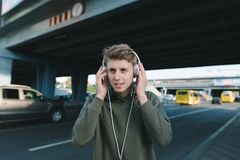 A positive young man is listening to music on the street in headphones on the background of architecture. Lifestyle and people con. A positive young man is Stock Photos