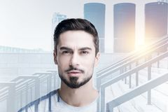 Positive young man looking at the pictures in a gallery and smiling Royalty Free Stock Image
