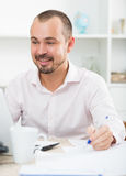 Positive young man in office Royalty Free Stock Photography