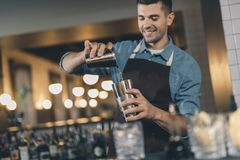 Positive young man pouring liquid into the cocktail shaker. Selective focus of a metal cocktail shaker and smiling bartender pouring liquid into it royalty free stock images