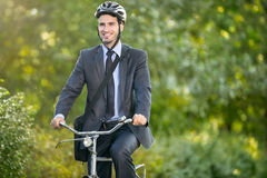 Positive young man riding a bicycle to work. Positive young man in suit and bicycle helmet riding a bicycle to work royalty free stock photography