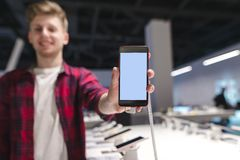 positive young man sends a smartphone with a white screen to the camera and smiles stock photo