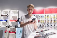 positive young man stands with a smartphone in the electronics store, looks at the camera and smiles royalty free stock image