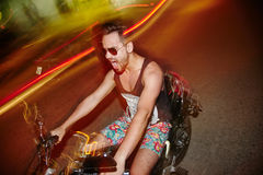 Positive young man in sunglasses riding a motorcycle in the night. Happy guy wearing casual t-shirt and sunglasses riding a motorcycle in the night royalty free stock photography