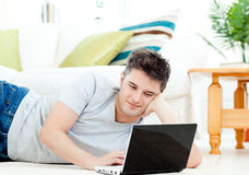 Positive young man using his laptop on the floor Stock Photography