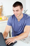 Positive young man using his laptop in the kitchen Stock Images