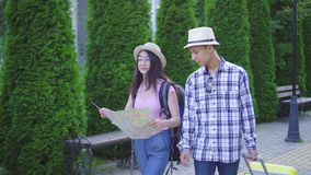 Positive young man and woman asian travelers with suitcase and card in hand in the park stock footage