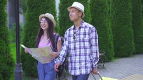 Positive young man and woman asian travelers with suitcase and card in hand in the park slow mo stock video footage