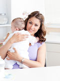 Positive young mother holding her baby. In the kitchen at home Royalty Free Stock Photos
