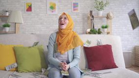 Positive young Muslim woman catches falling banknotes sitting on sofa at home. Close up stock video