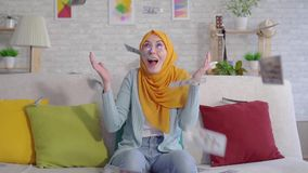 Positive young Muslim woman catches falling banknotes sitting on sofa at home close up. Slow mo stock footage