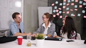 Positive young people laughing while working together during brainstorming sitting at the big white office table behind