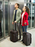 Positive young people with luggage standing. At metro terminal elevator Stock Images