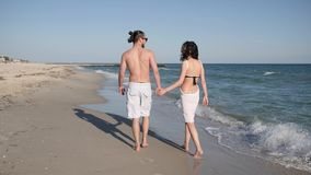 Positive young people in romantic walk, friends walking barefoot on sand, couple in love an exotic vacation, wind stock video