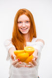 Positive young redhead woman offers oranges Stock Photos