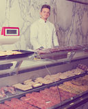 Positive young seller at butcher market Stock Images