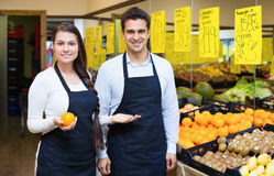 Positive young sellers offering good price for fruits Royalty Free Stock Photo