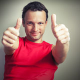 Positive young smiling man shows thumbs up Royalty Free Stock Image