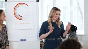 Positive young smiling manager business woman presenting project to partners at modern office sales team meeting. Happy beautiful blonde female finance expert stock video footage