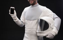 Positive young spaceman is demonstrating his smartphone stock photos