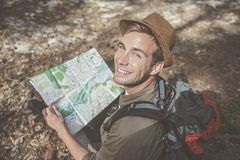 Positive young tourist is resting on ground. Happy look. Top view portrait of cheerful charming traveler wearing hat is sitting in woodland with backpack and Stock Image