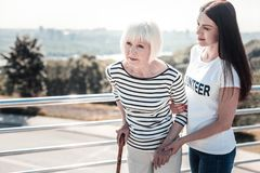 Positive young volunteer helping the elderly woman. Female volunteer. Positive nice young women holding an elderly womans hand and helping her to walk while Stock Photo