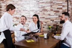 Positive young waiter receiving order from guests Royalty Free Stock Photography