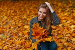 Positive young woman with a beautiful smile in a vintage coat in trendy jeans is sitting in the park on the background of golden stock image
