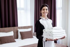 Positive young woman bringing fresh white towels royalty free stock image