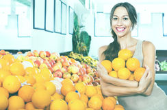 Positive young woman buying oranges Royalty Free Stock Images