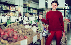 Positive young woman choosing seasonal vegetables in farm store stock images