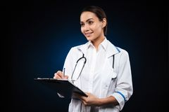 Positive young woman doctor writing in folder and looking aside