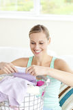 Positive young woman doing the laundry Stock Images
