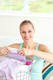 Positive young woman doing the laundry. At home Stock Photo