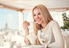 Positive young woman eating ice cream in light summer cafe Royalty Free Stock Photos
